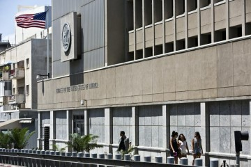 A security personnel stands outside the U.S. embassy in Tel Aviv as pedestrians walk past